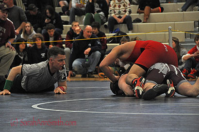 The ref is checking to see if John has his opponent's shoulders on the mat for a pin (he did)