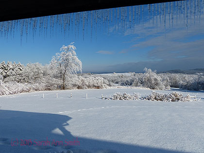 From the living room porch, with deck roof and icicles overhead, shadow of house in the foreground.