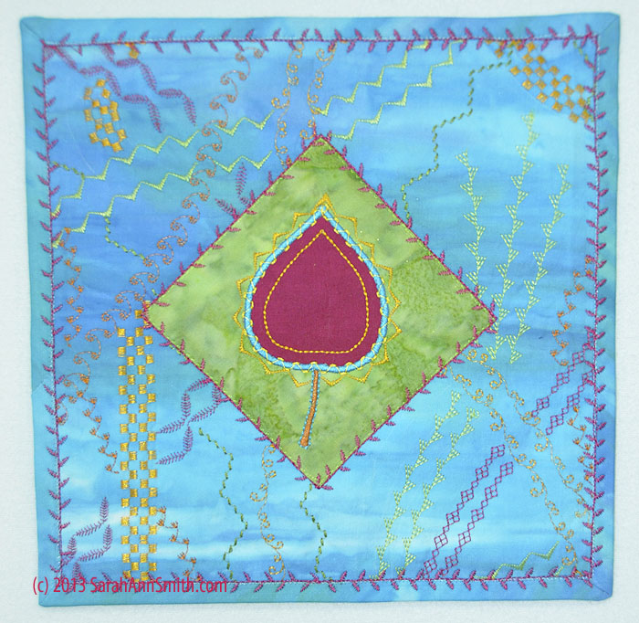 I made a smaller (about 9 inches square) quiltlet with the sampler leaf and the background stitching.  If you right click on this image, you can see more detail.  Notice how I layered up stitches to applique the green patch and how I used a decorative stitch on the binding.  On the latter, I used matching thread to machine stitch down the binding, then went over that with a decorative stitch.