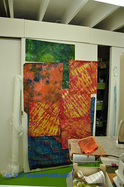 The green on the top is a hand-dye I like and want to reproduce.  The blue on the bottom is a purchased batik.  The pink-coral with blue splotches is the fugly piece just above.  The orange-fuchsia-yellow are that plum-mint ugliness.  The uglies are going back for more color.  Ugh.  They will make good browns eventually!