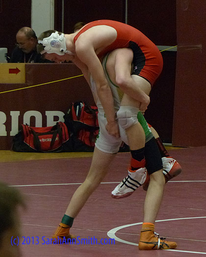 Earlier in the season, the kid from Massabesic tooled all over Eli at a duals (regular season) meet.  Eli was in a better frame of mind this day, but Eli told me the Massabesic kid is **really good** on his feet.  You don't often see Eli in this position, about to get dumped! (Eli is in red, Massabesic -- a Class A school from the southern part of the state -- is in white-green-yellow.