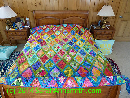Here's the quilt laid out on our queen sized bed.  It is about 86x97 inches.  I wish I'd made it one row wider, but by the time I figured that out the skinny half-triangles on the side were done, so I called it good!