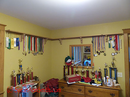 With medals hung, sorted by sport and year.  The wrestling pins need their own display--that's the next project.  And we think Eli is going to put his deceased running and wrestling shoes up on the shelf!