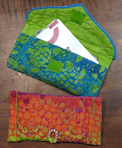 The blue-green card holder has velcro closing.  I painted white velcro with acrylic ink to match.  The warm-tones uses that thick hair elastic.  I like the way I used perle cotton to quilt the bag and stitch down the back end of the hair elastic.