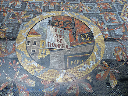 A pub sign that says Rest and be thankful in the mosaic floor.