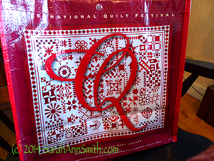 Barb Black's beautiful red and white quilt on the 40th Anniversary International Quilt Festival show bag.  GO BARB!