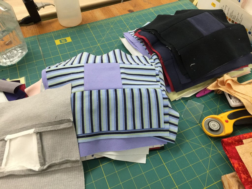 I've been piecing some blocks (who me?): made of turtleneck shirts. Eek! I had to stabilize all of them with interfacing (gray one in lower left corner). As expected, the machine breezed through without nary a burp.