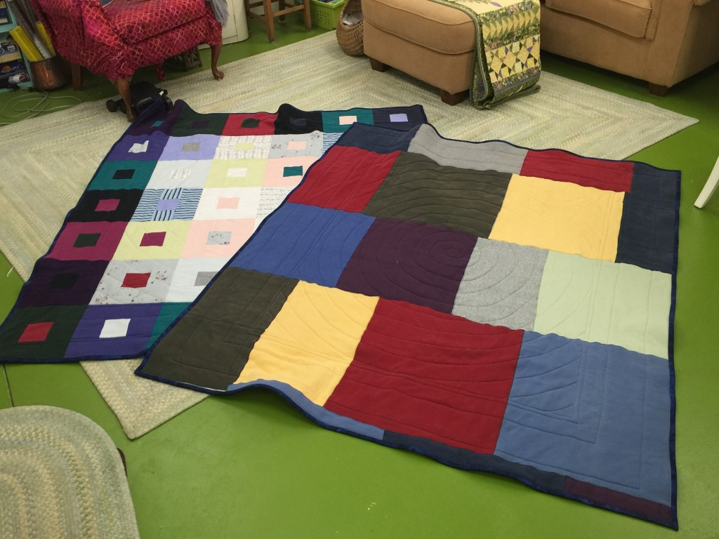 The two lap quilts, the one with the sweatshirts on the back is on the right, back side up. Can I just say it weighs a flipping TON!